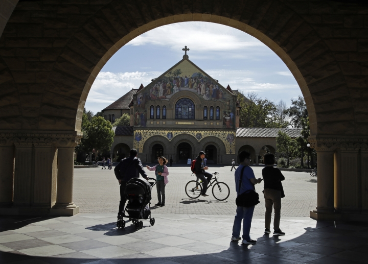 People walk near Memorial Church on the Stanford University campus Thursday, March 14, 2019, in Santa Clara, Calif. In the first lawsuit to come out of the college bribery scandal, several students are suing Yale, Georgetown, Stanford and other schools involved in the case, saying they and others were denied a fair shot at admission. The plaintiffs brought the class-action complaint Wednesday, March 13, 2019, in federal court in San Francisco on behalf of themselves and other applicants and asked for unspecified damages. (AP Photo/Ben Margot)
