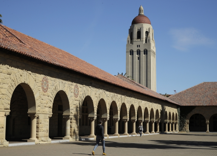 People walk on the Stanford University campus beneath Hoover Tower Thursday, March 14, 2019, in Santa Clara, Calif. In the first lawsuit to come out of the college bribery scandal, several students are suing Yale, Georgetown, Stanford and other schools involved in the case, saying they and others were denied a fair shot at admission. The plaintiffs brought the class-action complaint Wednesday, March 13, 2019, in federal court in San Francisco on behalf of themselves and other applicants and asked for unspecified damages. (AP Photo/Ben Margot)