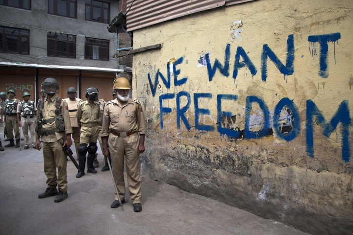 FILE - In this Aug. 12, 2016, file photo, Indian policemen stand guard during a curfew in Srinagar, Indian-controlled Kashmir. Indian Prime Minister Narendra Modi swept 2014 elections promising to reform India's economy, but his signature demonetization policy, intended to reduce money laundering, choke terrorist financing and boost digital payments, has been largely deemed a failure. But he seems to have regained ground after taking a tough stance in brinkmanship with Pakistan after a suicide bombing on Feb. 14, 2019, even though violence and massive protests continue to rock Indian-controlled Kashmir, where insurgent groups have been fighting for independence or a merger with Pakistan since 1989. (AP Photo/Dar Yasin, File)