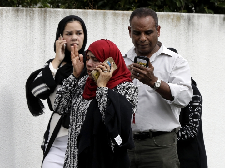 People wait outside a mosque in central Christchurch, New Zealand, Friday, March 15, 2019. Many people were killed in a mass shooting at a mosque in the New Zealand city of Christchurch on Friday, a witness said. Police have not yet described the scale of the shooting but urged people in central Christchurch to stay indoors. (AP Photo/Mark Baker)