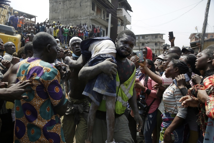 A body of a child is recovered from the rubble of a collapsed building in Lagos, Nigeria, Wednesday March 13, 2019. Rescue efforts are underway in Nigeria after a three-storey school building collapsed while classes were in session, with some scores of children thought to be inside at the time. (AP Photo/Sunday Alamba)