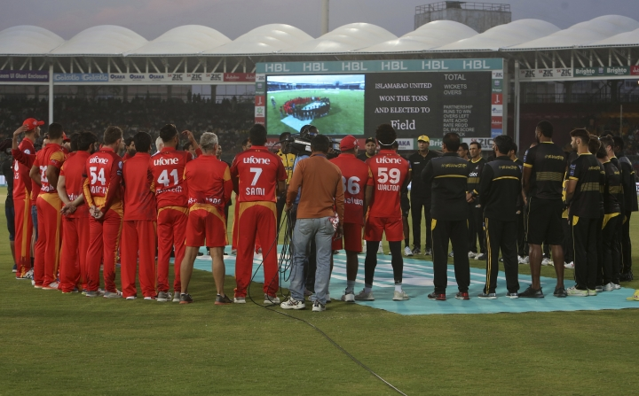 Players and officials of Islamabad United and Peshawar Zalmi observe a minute silence at National Stadium in Karachi on Friday, March 15, 2019 in memory of those who died in a deadly attacks on mosques in New Zealand. Islamabad plays Peshawar in Pakistan Super League eliminator 2. (AP Photo/Fareed Khan)