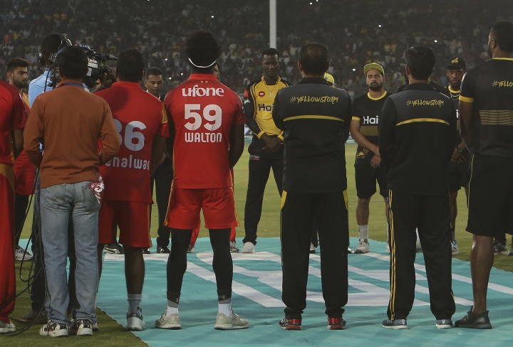 Darren Sammy, center, facing camera, joins other players and officials of Islamabad United and Peshawar Zalmi to observe a minute silence at National Stadium in Karachi, Pakistan, Friday, March 15, 2019 in memory of those who died in a deadly attacks on mosques in New Zealand. Islamabad plays Peshawar in Pakistan Super League eliminator 2. (AP Photo/Fareed Khan)