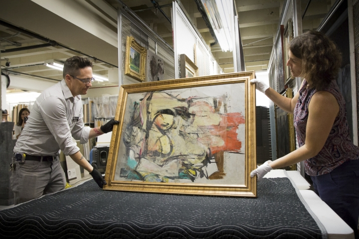 "This August 2017 photo shows ""Woman-Ochre,"" a painting by Willem de Kooning, being readied for examination by University of Arizona Museum of Art staff Nathan Saxton, left, and Kristen Schmidt in Tucson, Ariz. More than 30 years after it was stolen from the museum, the recovered painting will be on display back where it all began. (Robert Demers/University of Arizona Communications via AP)"
