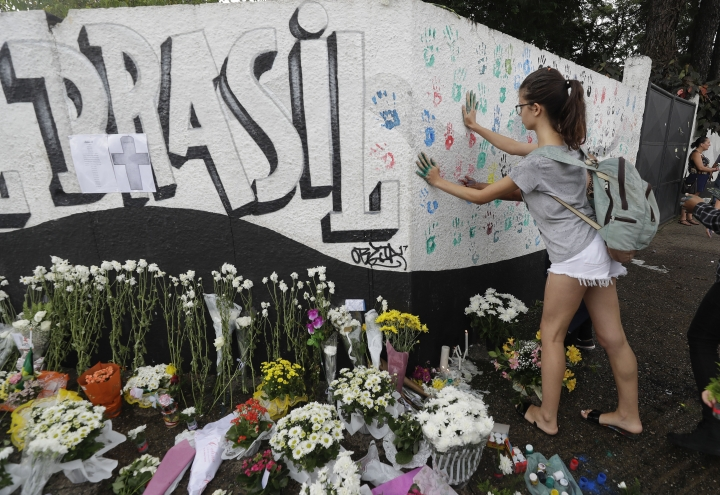 A student places her handprints on a wall at the Raul Brasil State School one day after a mass shooting, in Suzano, Brazil, Thursday, March 14, 2019. Classmates, friends and families began saying goodbye on Thursday, with thousands attending a wake in the Sao Paulo suburb while authorities worked to understand what drove two former students to attack the school with a gun, crossbows and small axes. (AP Photo/Andre Penner)