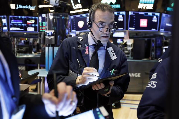FILE- In this March 5, 2019, file photo trader Gregory Rowe works on the floor of the New York Stock Exchange. The U.S. stock market opens at 9:30 a.m. EDT on Friday, March 15. (AP Photo/Richard Drew, File)