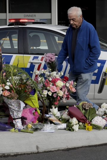 A men places flowers at a makeshift memorial near the Masjid Al Noor mosque in Christchurch, New Zealand, Saturday, March 16, 2019, where one of the mass shootings occurred yesterday. (AP Photo/Mark Baker)