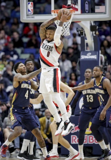 Portland Trail Blazers guard Damian Lillard (0) grabs a rebound against New Orleans Pelicans guard Elfrid Payton (4) in the first half of an NBA basketball game in New Orleans, Friday, March 15, 2019. (AP Photo/Scott Threlkeld)