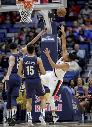 Portland Trail Blazers guard CJ McCollum (3) is fouled by New Orleans Pelicans center Jahlil Okafor (8) as guard Frank Jackson (15) trails the play in the first half of an NBA basketball game in New Orleans, Friday, March 15, 2019. (AP Photo/Scott Threlkeld)