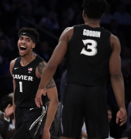 Xavier guard Paul Scruggs (1) reacts with teammate Quentin Goodin (3) after scoring a basket on Villanova during the first half of an NCAA college basketball semifinal game in the Big East men's tournament, Friday, March 15, 2019, in New York. (AP Photo/Julio Cortez)