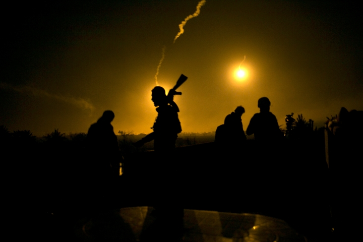 FILE - In this Tuesday, March 12, 2019 file photo, a U.S.-backed Syrian Democratic Forces (SDF) fighter watches illumination rounds light up Baghouz, Syria, as the last pocket of Islamic State militants is attacked. As Syria marks the eighth anniversary of its grinding war, Syrian President Bashar Assad's government appears to have won the war against the insurgency trying to topple him. While the Islamic State group's territorial defeat will close one of its bloody conflicts, others are still burning. (AP Photo/Maya Alleruzzo, File)