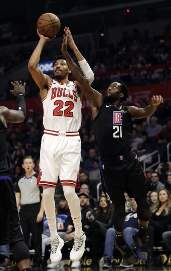 Chicago Bulls' Otto Porter Jr. (22) shoots next to Los Angels Clippers' Patrick Beverley (21) during the first half of an NBA basketball game Friday, March 15, 2019, in Los Angeles. (AP Photo/Marcio Jose Sanchez)