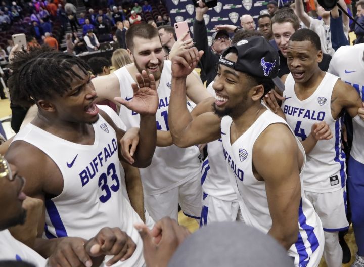 Buffalo's CJ Massinburg, right, Nick Perkins, left, and teammates celebrate after Buffalo defeated Bowling Green 87-73 in an NCAA college basketball game for the Mid-American Conference men's tournament title Saturday, March 16, 2019, in Cleveland. (AP Photo/Tony Dejak)