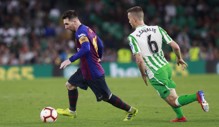 Barcelona's Lionel Messi and Betis' Canales, right, challenge for the ball during La Liga soccer match between Betis and Barcelona at the Benito Villamarin stadium in Seville, Spain, Sunday, March 17, 2019. (AP Photo/Miguel Morenatti)