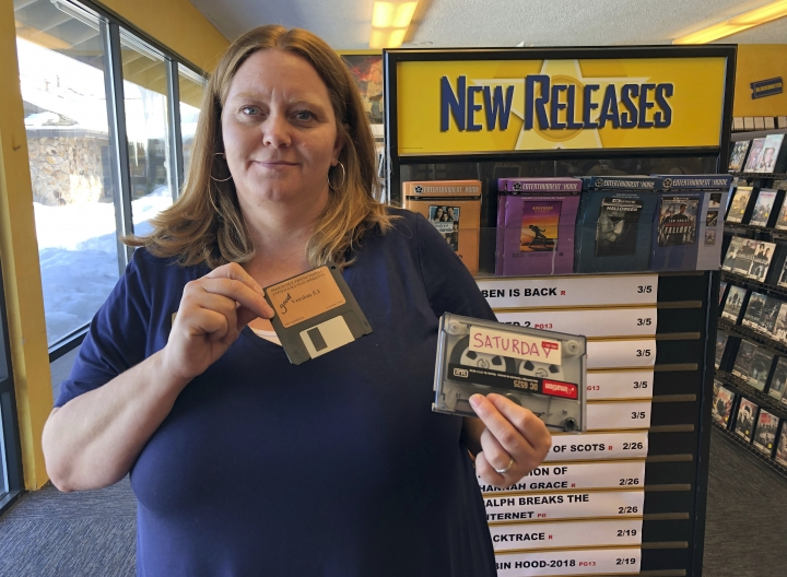 Sandi Harding, general manager of the last Blockbuster on the planet in Bend, Ore., poses for a photo inside the store on Monday, March 11, 2019. Harding is holding up the floppy disc she uses to reboot her computer and the reel-to-reel tape used to back up transactions. When a Blockbuster in Perth, Australia, shuts its doors for the last time on March 31, the store in Bend, Ore., will be the only one left on Earth, and most likely in the universe. (AP Photo/Gillian Flaccus)