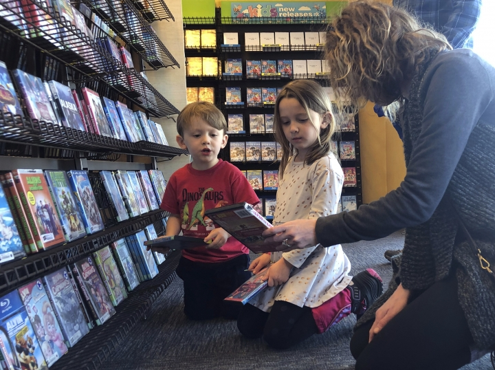 Elizabeth Gilless, of Memphis, Tenn., shows her children John, 3, and Ellen, 5, a movie from the children's section at the last Blockbuster on the planet in Bend, Ore., on Tuesday, March 12, 2019. The family was vacationing in Oregon and stopped by the store to buy souvenirs on their way to Portland, Ore., after hearing it was the last Blockbuster on the planet. When a Blockbuster in Perth, Australia, shuts its doors for the last time on March 31, the store in Bend, Ore., will be the only one left on Earth, and most likely in the universe. (AP Photo/Gillian Flaccus)