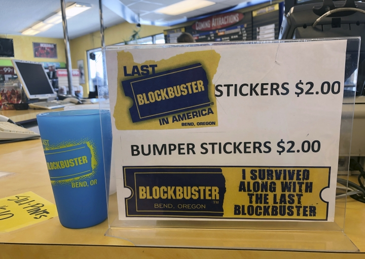 A sign advertising locally made souvenirs from the last Blockbuster store on the planet sits in the store in Bend, Ore., in this Tuesday, March 12, 2019 photo. When a Blockbuster in Perth, Australia, shuts its doors for the last time on March 31, the store in Bend, Ore., will be the only one left on Earth, and most likely in the universe. (AP Photo/Gillian Flaccus)