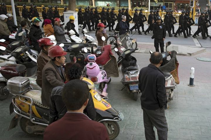 """FILE - In this Nov. 5, 2017, file photo, residents watch a convoy of security personnel armed with batons and shields patrol through central Kashgar in western China's Xinjiang region. China says on Monday, March 18, 2019 it has arrested nearly 13,000 people it describes as terrorists in the traditionally Islamic region of Xinjiang since 2014 and broken up hundreds of """"terrorist gangs."""" The figures were included in a government report on the situation in the restive northwestern territory that seeks to respond to growing criticism over the internment of an estimated 1 million members of the Uighur (WEE-gur) and other predominantly Muslim ethnic groups. (AP Photo/Ng Han Guan, File)"""