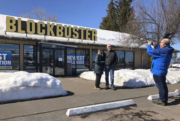 Debby Saltzman, of Bend, Ore., poses for a photo on Monday, March 11, 2019, in front of the last Blockbuster store on the planet with her twin brother, Michael Trovato. Trovato was visiting from Melbourne, Australia, where he lives. Taking the photo is Saltzman's husband, Jeremy Saltzman. When a Blockbuster in Perth, Australia, shuts its doors for the last time on March 31, the store in Bend, Ore., will be the only one left on Earth, and most likely in the universe. (AP Photo/Gillian Flaccus)
