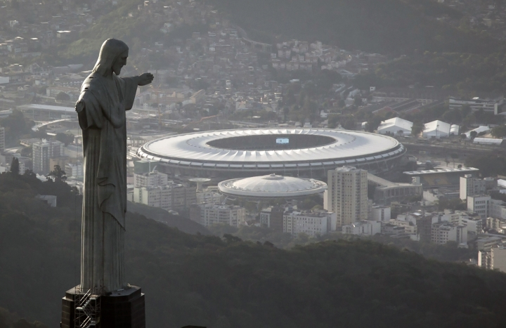 FILE - This May 13, 2014, file photo, the Maracana stadium behind the Christ the Redeemer statue, in Rio de Janeiro, Brazil. Gov. Wilson Witzel said in a press conference Monday March 18, 2019, that the group running the 78,000-seat Maracana stadium owes the state around dollars 10 million and that Rio de Janeiro's state government will take back control of the crisis-ridden facility. (AP Photo/Felipe Dana, File)