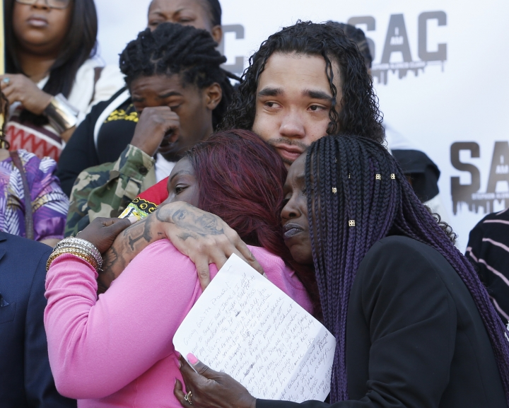 Trayvon Wiseman, center, a cousin of police shooting victim Stephon Clark, hugs Clark's mother, SeQuette Clark, left, and grandmother, Sequitta Thompson, right, during a news conference at the Capitol on vMonday, March 18, 2019, in Sacramento, Calif. Monday marks a year since two Sacramento police officers killed Clark, 22, in Thompson's backyard as they responded to vandalism reports. (AP Photo/Rich Pedroncelli)