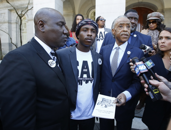 The Rev. Al Sharpton, second from right, accompanied by Stevante Clark, center, the brother of police shooting victim Stephon Clark, and attorney Benjamin Crump, left, talks to reporter after a news conference Monday, March 18, 2019, in Sacramento, Calif. Sharpton called for California to change how it responds to police killings of civilians as Monday marks a year since two Sacramento police officers killed Clark, 22, as they responded to vandalism reports. (AP Photo/Rich Pedroncelli)