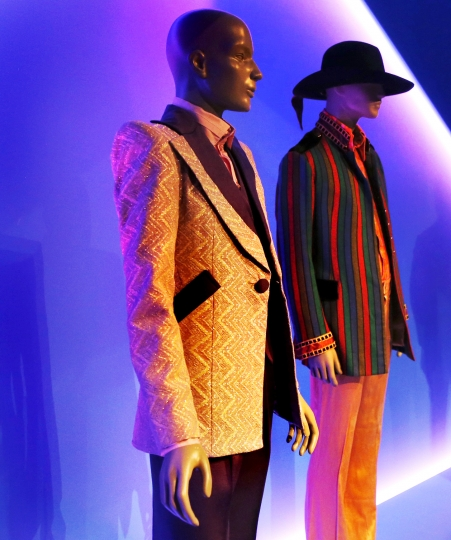 """In this Thursday, March 14, 2019, photo, a suit worn by David Bowie, left, is displayed next to an ensemble worn by Jimi Hendrix for the """"Gender Bending Fashion"""" exhibition at the Museum of Fine Arts in Boston. The new exhibit at the museum explores how blurring gender lines are redefining the fashion industry. The show opens to the public on Thursday, March 21, and examines moments in history when clothing transcended and muddled our understanding of gender. (AP Photo/Charles Krupa)"""
