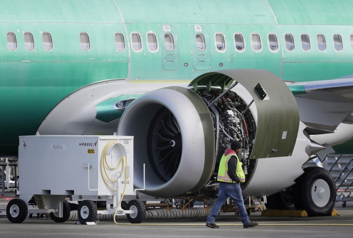 """FILE- In this March 13, 2019, file photo a worker walks past an engine on a Boeing 737 MAX 8 airplane being built for American Airlines at Boeing Co.'s Renton assembly plant in Renton, Wash. U.S. prosecutors are looking into the development of Boeing's 737 Max jets, a person briefed on the matter revealed Monday, the same day French aviation investigators concluded there were """"clear similarities"""" in the crash of an Ethiopian Airlines Max 8 last week and a Lion Air jet in October. (AP Photo/Ted S. Warren, File)"""