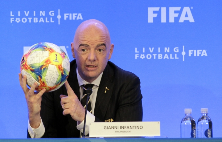 FIFA President Gianni Infantino holds a soccer ball as he speaks during a press conference after the FIFA Council Meeting, Friday, March 15, 2019, in Miami. The council approved working with Qatar to explore expanding the 2022 World Cup to 48 teams by adding at least one more country in the Persian Gulf to host matches. (AP Photo/Luis M. Alvarez)