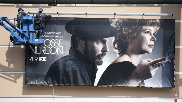 """Workers put up a poster for the upcoming FX limited series """"Fosse/Verdon"""" near the entrance to Fox Studios, Tuesday, March 19, 2019, in Los Angeles. Disney's $71.3 billion acquisition of Fox's entertainment assets is set to close around 12 a.m. EDT on Wednesday.(AP Photo/Chris Pizzello)"""