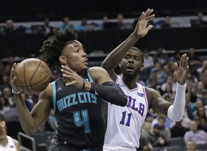 Charlotte Hornets' Devonte' Graham (4) looks to pass as Philadelphia 76ers' James Ennis III (11) defends during the first half of an NBA basketball game in Charlotte, N.C., Tuesday, March 19, 2019. (AP Photo/Chuck Burton)
