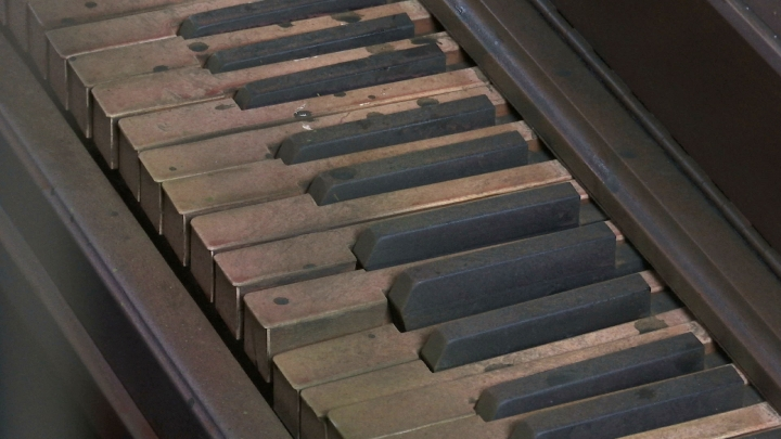In this March 15, 2019 image taken from video, piano keys, stained and damaged to look as though they were in a once-flooded room, part of a re-creation of flood damage in a new exhibit in New Orleans by the organization Levees.org. The organization is unveiling the exhibit Saturday, March 23, in a house near the site of one of the floodwall failures that led to inundation of New Orleans when Hurricane Katrina struck in 2005. (AP Photo/Stacey Plaisance)