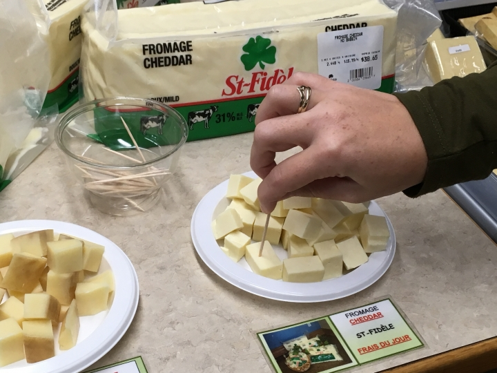 In this Sept. 19, 2018 photo, a tourist tries a sample of cheese from the Fromagerie Saint-Fidele in Saint-Fidele, Quebec in Canada. Fromagerie Saint-Fidele makes cheeses with terroir accents, offering fresh cheddar and Swiss to customers each day. (AP Photo/John Marshall)
