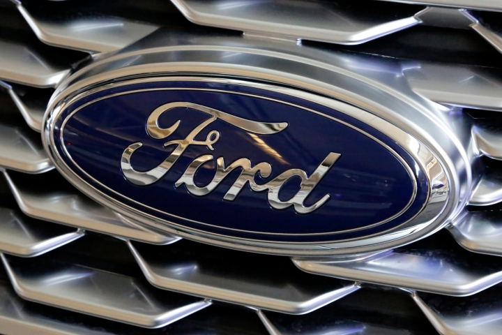 FILE- This Feb. 15, 2018, file photo shows a Ford logo on the grill of a car on display at the Pittsburgh Auto Show. Ford Motor Co. is repackaging a previously announced manufacturing investment in the Detroit area and now says it will spend $900 million and create 900 new jobs over the next four years. Most of the new workers will build a new generation of electric vehicle at Ford's existing factory in Flat Rock, Michigan, south of Detroit, which will see an $850 million investment. (AP Photo/Gene J. Puskar, File)