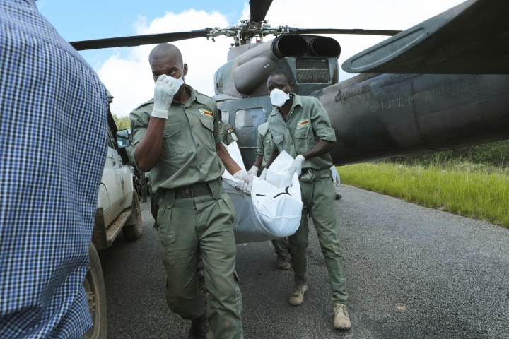 Rescuers carry a body from a military helicopter in Chimanimani, about 600 km south east of Harare, Zimbabwe, Wednesday, March, 20, 2019. Zimbabwean President Emmerson Mnangagwa visited a part of Chimanimnani affected by cyclone Idai and promised assistance in the form of food and rebuilding of homes. Hundreds are dead, many more missing and thousands at risk from massive flooding in Mozambique, Malawi and Zimbabwe caused by Cyclone Idai. (AP Photo/Tsvangirayi Mukwazhi)