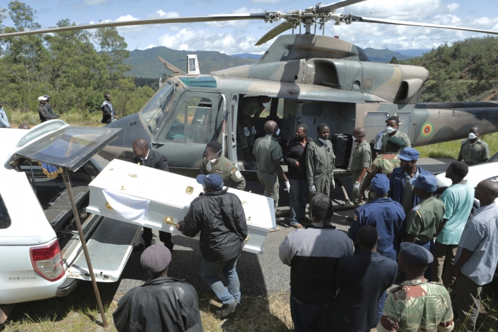 Rescuers carry a body from a military helicopter into a waiting hearse in Chimanimani, about 600 km south east of Harare, Zimbabwe, Wednesday March 20, 2019. Zimbabwean President Emmerson Mnangagwa visited a part of Chimanimnani affected by cyclone Idai and promised assitance in the form of food and rebuilding of homes. Hundreds are dead, many more missing and thousands at risk from massive flooding in Mozambique, Malawi and Zimbabwe caused by Cyclone Idai. (AP Photo/Tsvangirayi Mukwazhi)
