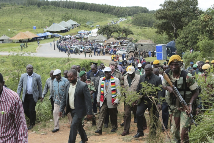 Zimbabwean President Emmerson Mnangagwa, center with scarf, visits Chimanimani about 600 km south east of Harare, Zimbabwe, Wednesday March 20, 2019. Mnangagwa visited a part of Chimanimnani affected by cyclone Idai and promised assitance in the form of food and rebuilding of homes. Hundreds are dead, many more missing and thousands at risk from massive flooding in Mozambique, Malawi and Zimbabwe caused by Cyclone Idai. (AP Photo/Tsvangirayi Mukwazhi)