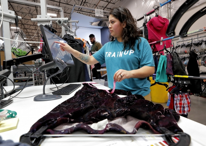 """In this Tuesday, March 12, 2019, photo Jasmine Valladares enters measurements as she itemizes clothing at the ThredUp sorting facility in Phoenix. Charitable organizations like Goodwill have cited how Marie Kondo's popular Netflix series, """"Tidying up with Marie Kondo"""" has led to a surge of donations. And sites like OfferUp and thredUP also note an uptick in the number of items being sent to them for sale. (AP Photo/Matt York)"""