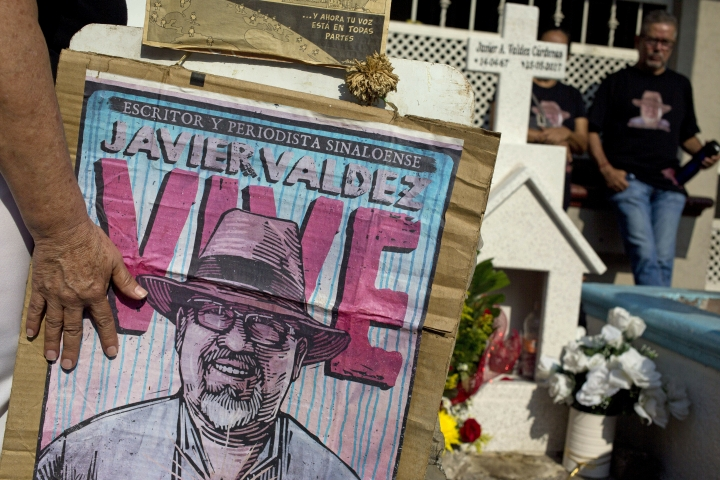 FILE - In this July 1, 2017 file photo, relatives of slain journalist Javier Valdez, co-founder of Riodoce, stand at a memorial set up at the spot where he was murdered in Culiacan, Sinaloa state, Mexico. Valdez's widow was the target of an attempted spyware attack 10 days after her husband's slaying, according to a report by Toronto-based internet watchdog Citizen Lab presented Wednesday, March 20, 2019, which brings to 25 the number of known cases involving Pegasus spyware, including two of Valdez's colleagues at the Riodoce weekly. (AP Photo/Enric Marti, File)