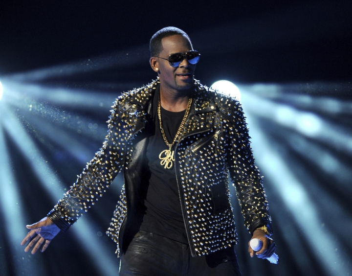 FILE - In this June 30, 2013 file photo, R. Kelly performs at the BET Awards in Los Angeles. Kelly has asked the Chicago judge to let him travel overseas for concerts in Dubai, saying he's been unable to get work anywhere in the U.S. since his arrest on charges he sexually abused three minor girls and an adult woman. The request in a Wednesday filing says the R&B star will perform at up to five concerts in the oil-rich nation in the Middle East. A judge ordered Kelly to surrender his passport after his arrest last month on 10 counts of aggravated sexual abuse. (Photo by Frank Micelotta/Invision/AP, File)