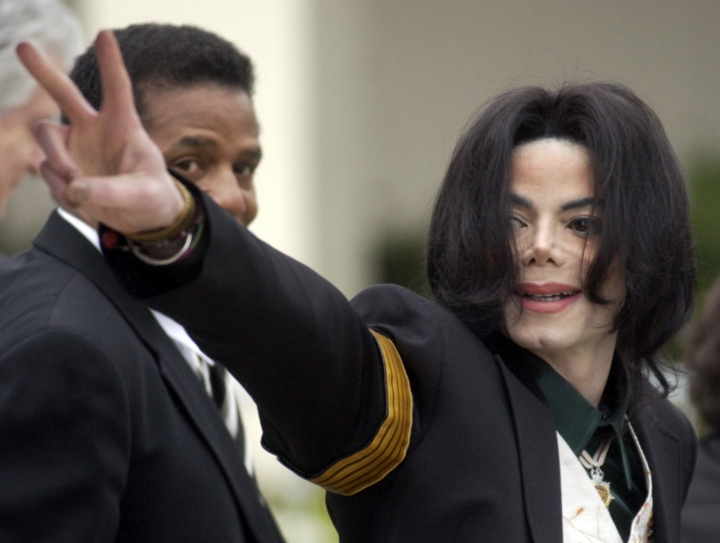"FILE - In this March 2, 2005, file photo, pop icon Michael Jackson waves to his supporters as he arrives for his child molestation trial at the Santa Barbara County Superior Court in Santa Maria, Calif. A new documentary on HBO, ""Leaving Neverland,"" is about the abuse allegations of two men, Wade Robson and James Safechuck, who had previously denied Jackson molested them and supported him to authorities and in Robson's case, very publicly. (AP Photo/Michael A. Mariant, File)"