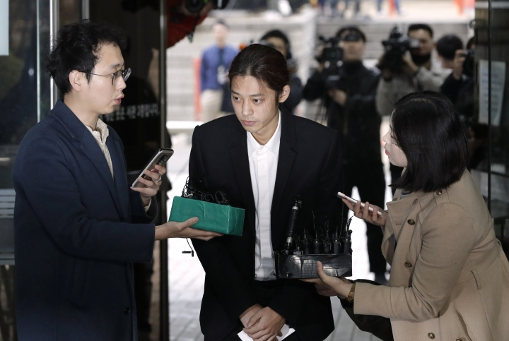 K-pop singer Jung Joon-young is questioned by reporters upon his arrival to attend a hearing at the Seoul Central District Court in Seoul, South Korea, Thursday, March 21, 2019. A South Korean pop star has appeared at a court hearing to decide whether to arrest him over allegations that he illegally shared sexually explicit videos of women taken without their knowledge or consent in online group chats. (AP Photo/Lee Jin-man)