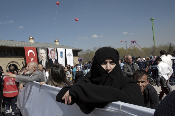 A woman tries to see Turkey's President Recep Tayyip Erdogan during the inauguration of a theme park in Ankara, Turkey, Wednesday, March 20, 2019. Erdogan has sparked a diplomatic spat with New Zealand and Australia as he campaigns for votes in local elections this month and portrays the mosque shooting in New Zealand and a World War I battle as targeting Islam.(AP Photo/Burhan Ozbilici)