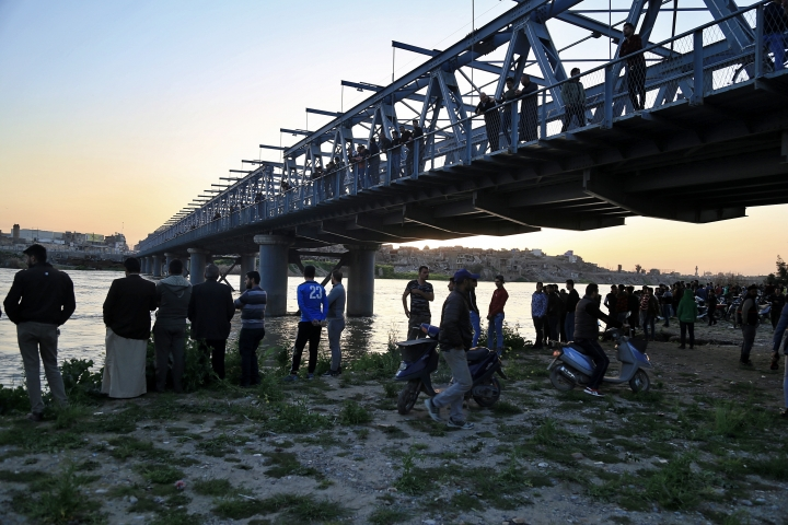 People and relatives of victims waiting on the bank of the Tigris river where the ferry sank in Mosul, Iraq, Thursday, March 21, 2019. A ferry overloaded with people celebrating the Kurdish new year sank in the Tigris River near the Iraqi city of Mosul on Thursday, killing dozens of people, mostly women and children, officials said. (AP Photo/Farid Abdulwahed)