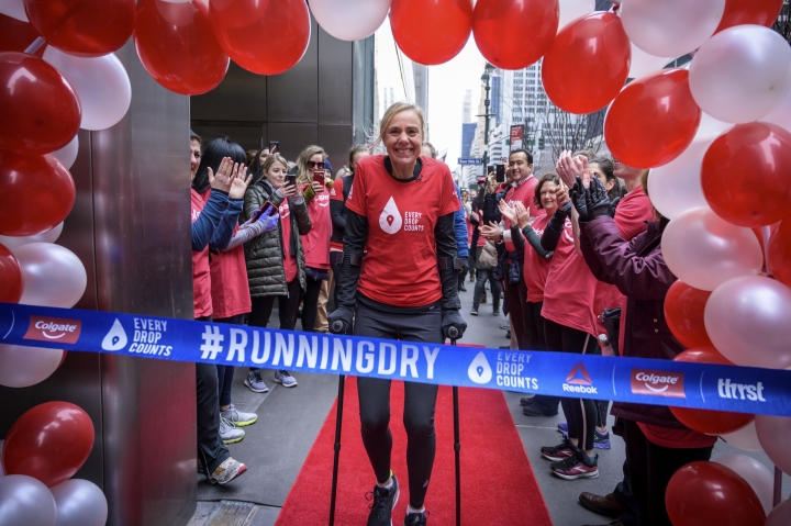 This Feb. 11, 2019, photo provided by Colgate, shows ultra-marathoner and water activist Mina Guli, aided by canes, approaching a ceremonial finish line in New York. Gulia came close to running 100 marathons in 100 days over sever continents, all in an effort to raise awareness about global water shortages and how to prevent them. (Kelvin Trautman/Colgate via AP)
