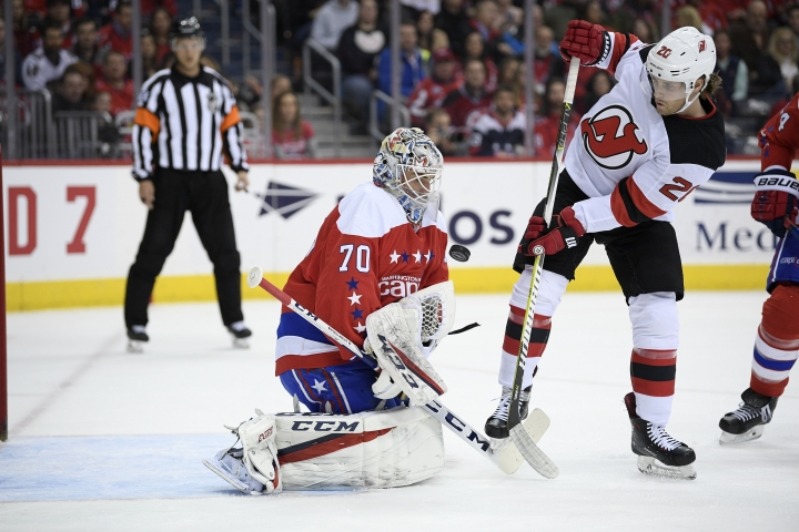 Washington Capitals goaltender Braden Holtby (70) tries to corral the puck, next to New Jersey Devils center Blake Coleman (20) during the first period of an NHL hockey game Friday, March 8, 2019, in Washington. (AP Photo/Nick Wass)