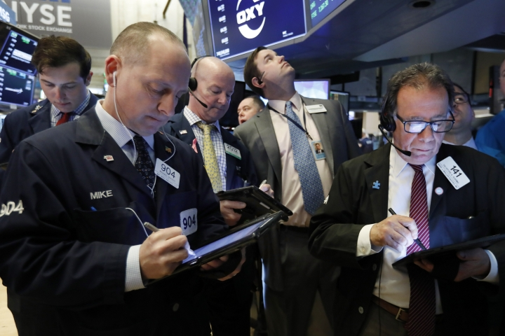 FILE- In this March 13, 2019, file photo traders gather at the post that handles Oaktree Capital Group on the floor of the New York Stock Exchange. The U.S. stock market opens at 9:30 a.m. EDT on Friday, March 22. (AP Photo/Richard Drew, File)