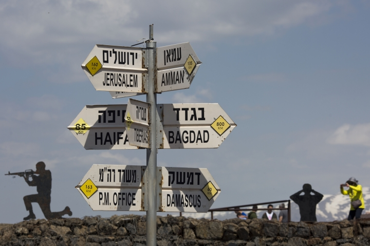 Tourists take photographs next to a mock road sign for Damascus, the capital of Syria, and other capitals and cities and a cutout of a soldiers, in an old outpost in the Israeli controlled Golan Heights near the border with Syria, Friday, March 22, 2019. President Donald Trump abruptly declared Thursday the U.S. will recognize Israel's sovereignty over the disputed Golan Heights, a major shift in American policy that gives Israeli Prime Minister Benjamin Netanyahu a political boost a month before what is expected to be a close election.(AP Photo/Ariel Schalit)