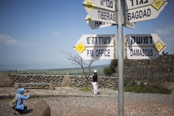 Tourists pose for photograph next to a mock road sign for Damascus, the capital of Syria, and other capitals and cities and a cutout of a soldier, in an old outpost in the Israeli controlled Golan Heights near the border with Syria, Friday, March 22, 2019. President Donald Trump abruptly declared Thursday the U.S. will recognize Israel's sovereignty over the disputed Golan Heights, a major shift in American policy that gives Israeli Prime Minister Benjamin Netanyahu a political boost a month before what is expected to be a close election.(AP Photo/Ariel Schalit)