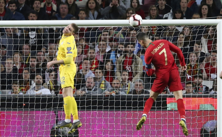 Portugal's Cristiano Ronaldo, right, tries to head the ball during the Euro 2020 group B qualifying soccer match between Portugal and Ukraine at the Luz stadium in Lisbon, Friday, March 22, 2019. (AP Photo/Armando Franca)